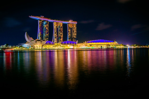 Edifícios da paisagem urbana de noite de singapura na área de marina bay singapura Foto Premium