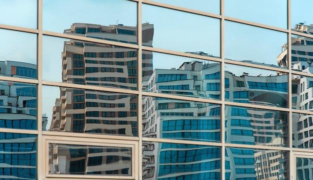 Edifícios modernos curvados refletidos nas janelas espelhadas Foto Premium