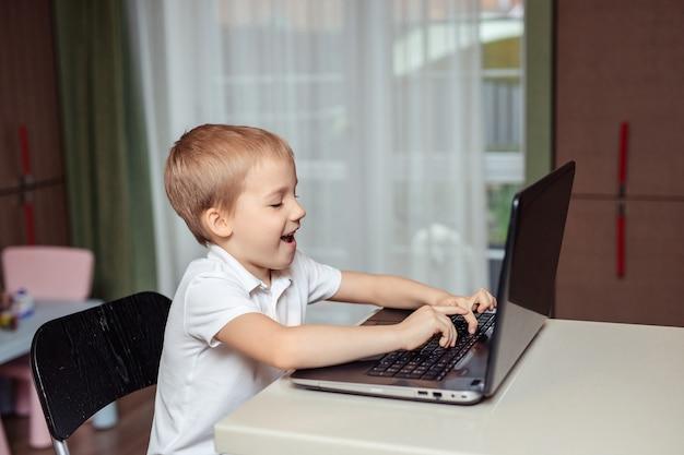 Educação domiciliar à distância de crianças em quarentena. menino feliz no polo branco fazendo lição de casa usando laptop sentado em casa na cozinha Foto Premium