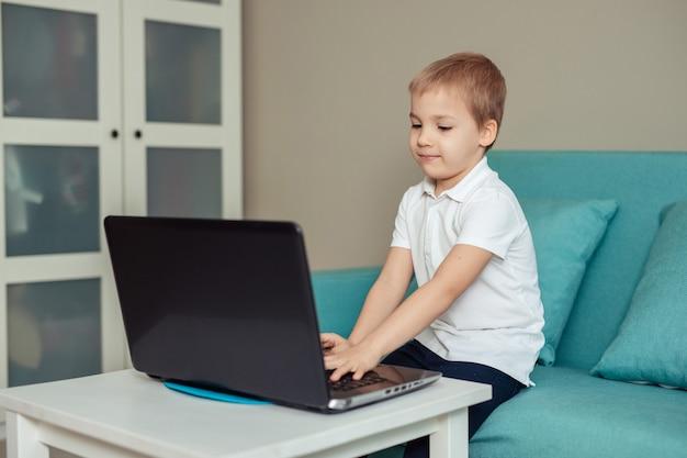 Educação domiciliar à distância de crianças em quarentena. menino feliz no polo branco fazendo lição de casa usando laptop sentado no sofá Foto Premium