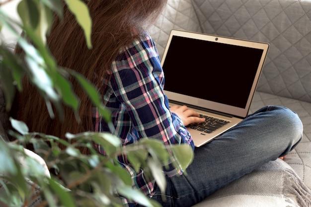 Educação e trabalho on-line a distância. menina mulher recortada senta câmera traseira de casa no sofá. usando laptop Foto Premium