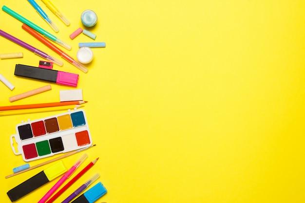 Educação e volta ao conceito de escola. material escolar para desenho sobre um fundo amarelo. vista superior, lay plana. Foto Premium