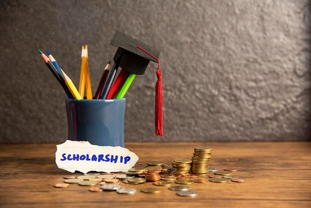 Educação e volta para a escola com chapéu de formatura na cor de lápis em uma caixa de lápis em bolsas de estudo escuras Foto Premium