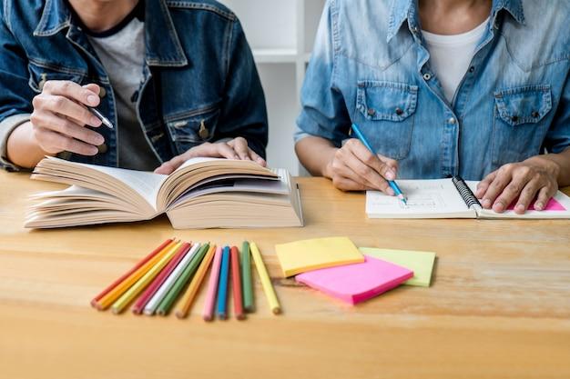 Educação, ensino, aprendizagem, tecnologia e conceito de pessoas. dois alunos do ensino médio ou colegas de turma com ajuda amigo fazem lição de casa aprendendo em sala de aula, livros de tutor com os amigos Foto Premium