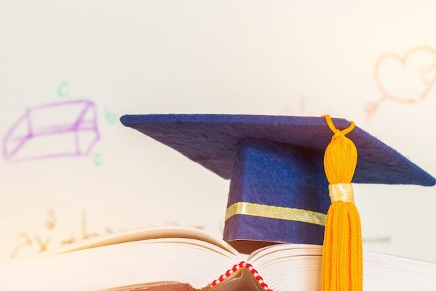 Educação graduado capelo chapéu azul no livro didático com fórmula equação ou matemática na tela Foto Premium