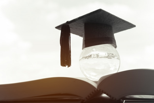 Educação no global, tampão da graduação na bola de cristal superior no livro de texto. Foto Premium