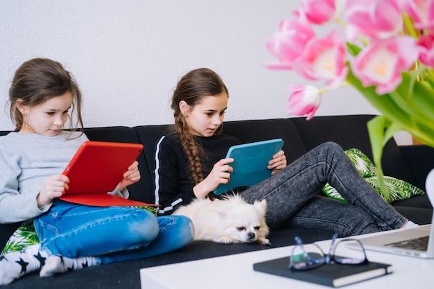 Educação on-line, ensino a distância, ensino em casa. crianças estudando a lição de casa durante a aula on-line em casa no tablet do laptop e segurando a videochamada. distância social em quarentena. isolamento voluntário Foto Premium