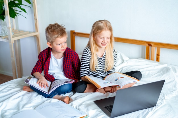 Educação online a distância. estudante e garota estudando em casa com o notebook laptop tablet digital e fazendo lição de casa da escola. sentado na cama com livros de treinamento. Foto Premium