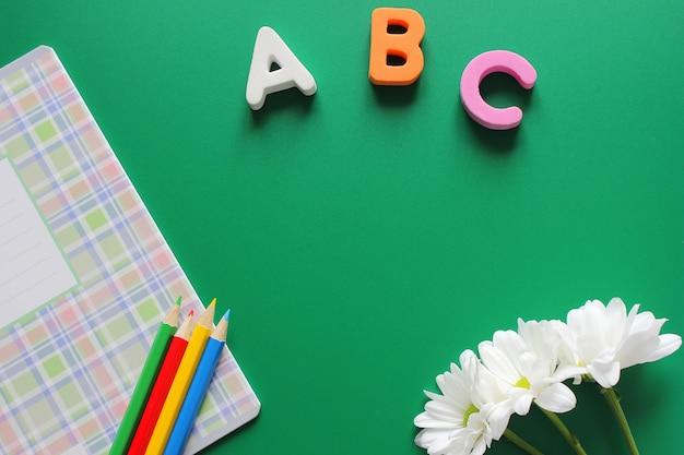 Eduque o caderno e os lápis coloridos ao lado das letras abc e crisântemos brancos em um fundo verde. Foto Premium