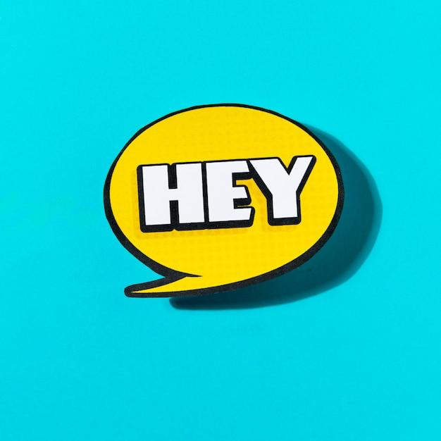 Ei texto no balão amarelo sobre fundo azul Foto gratuita