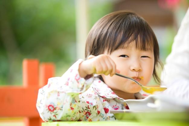 Ela é uma criança adorável sentada ao lado de sua mãe e comendo sopa. Foto Premium