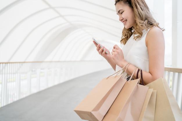 Ela faz compras no shopping e usa um telefone celular para se comunicar com amigos e usa sacolas de papel para fazer compras. Foto Premium