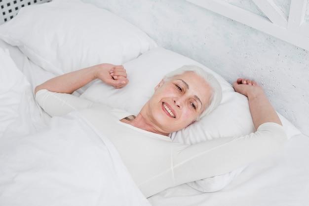 Elder mulher acordar na cama Foto gratuita