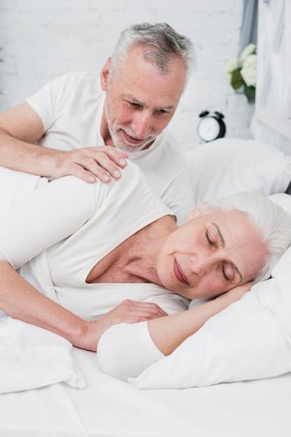 Elder mulher dormindo em uma cama branca Foto gratuita