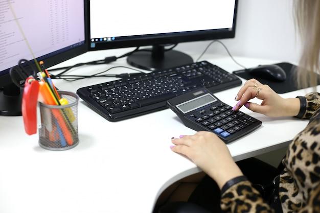 Ele conta os números na calculadora perto do monitor do computador Foto Premium