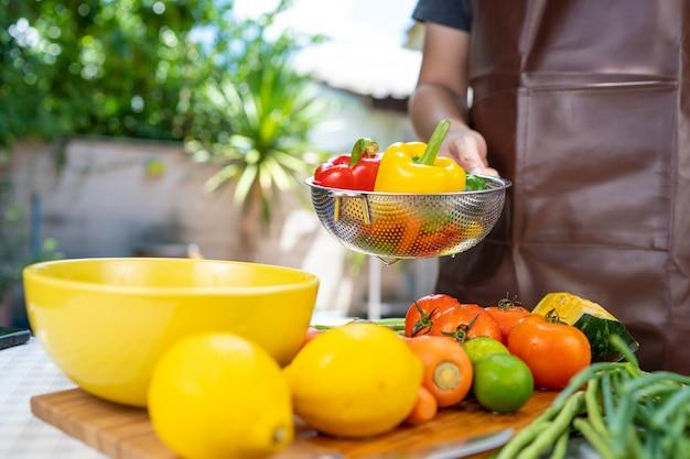 Ele está lavando frutas e legumes. Foto Premium
