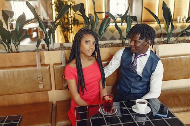 Elegante casal preto sentado em um café e tomando um café Foto gratuita