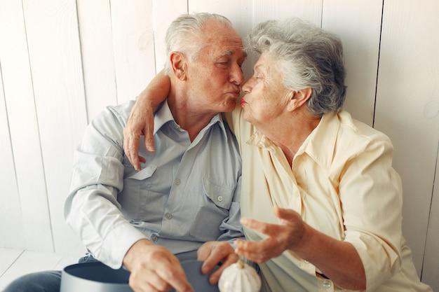 Elegante casal velho sentado em casa com presentes de natal Foto gratuita