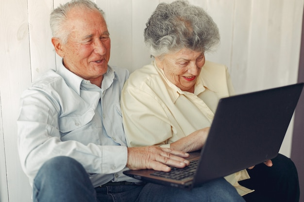 Elegante casal velho sentado em casa e usando um laptop Foto gratuita