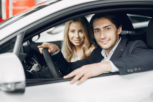 Elegante e elegante casal em um salão de beleza do carro Foto gratuita
