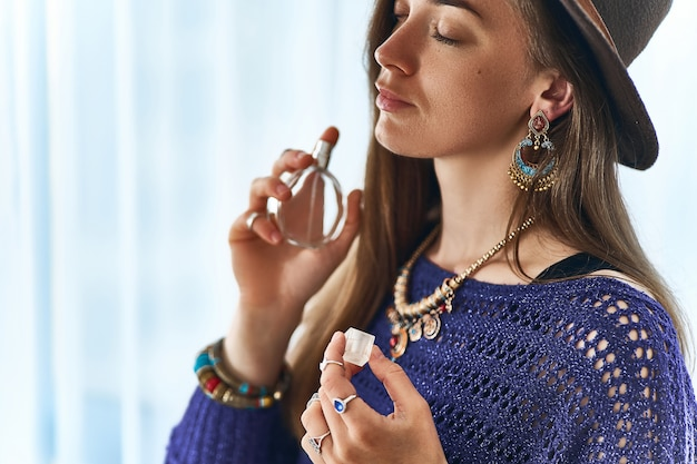 Elegante elegante atraente morena boho chic mulher com os olhos fechados, usando jóias e chapéu aplicar perfume de perfume de mulheres Foto Premium
