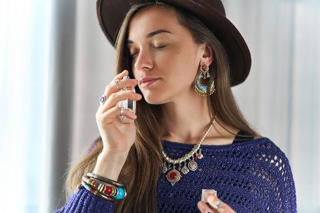 Elegante elegante atraente morena boho mulher chique com os olhos fechados, usando jóias e chapéu goza de perfume perfume Foto Premium