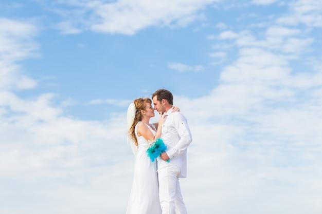 Elegante elegante noiva feliz e lindo noivo no fundo do céu azul Foto Premium