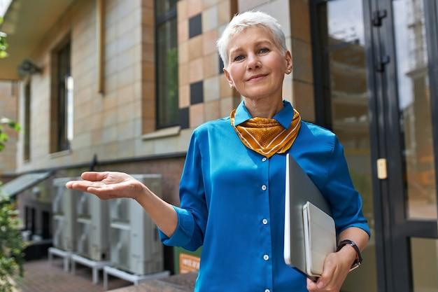 Elegante empresária de meia-idade confiante com penteado curto, posando do lado de fora do prédio de escritórios com o laptop debaixo do braço, fazendo um gesto como se estivesse segurando algo Foto gratuita