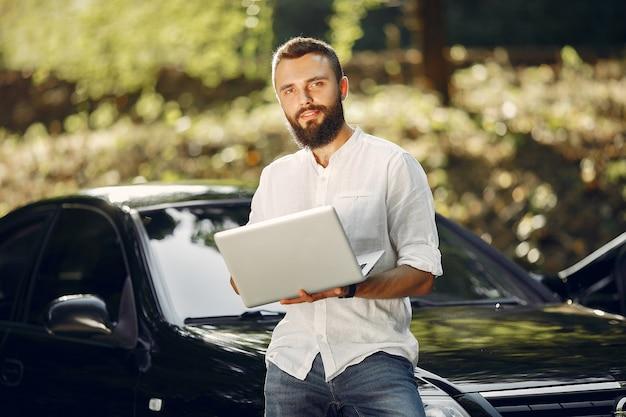 Elegante empresário de pé perto do carro e use o laptop Foto gratuita