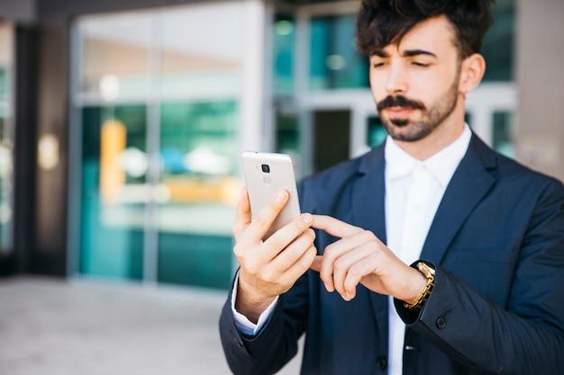 Elegante empresário olhando para o smartphone Foto gratuita