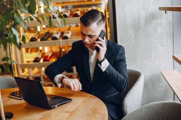Elegante empresário trabalhando em um café Foto gratuita
