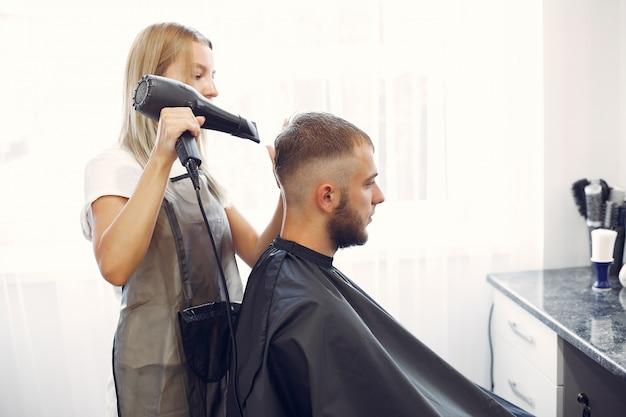 Elegante homem sentado em uma barbearia Foto gratuita