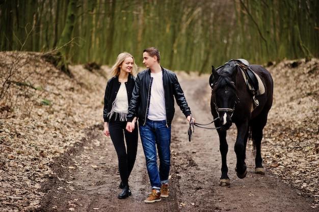 Elegante jovem casal apaixonado andando com cavalo na floresta de outono Foto Premium