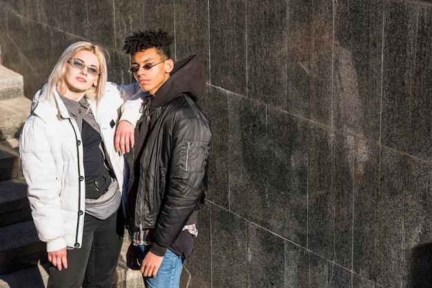 Elegante jovem casal usando óculos de sol em pé ao ar livre Foto gratuita
