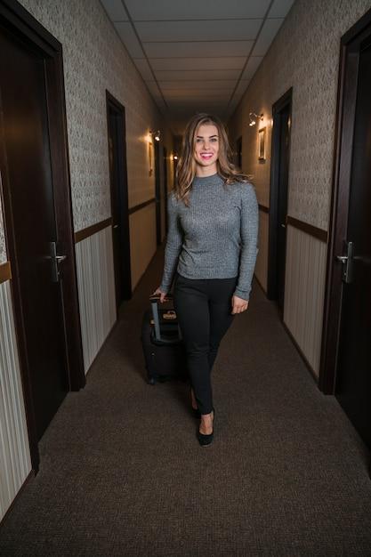 Elegante jovem com saco de bagagem andando no corredor do hotel Foto gratuita