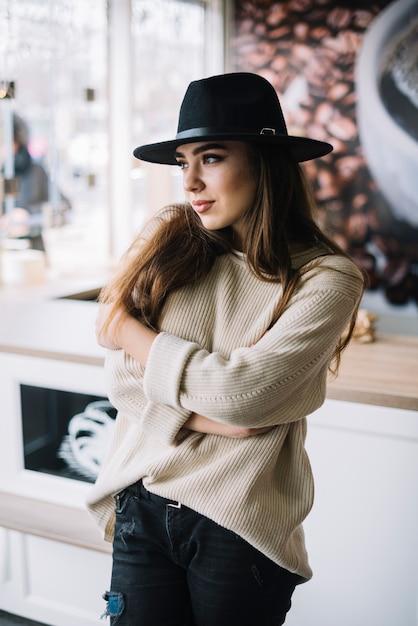 Elegante jovem de chapéu com as mãos cruzadas Foto gratuita