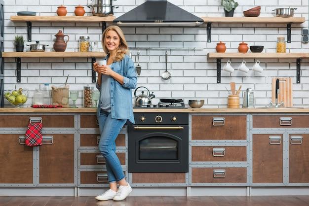 Elegante jovem de pé na cozinha modular, segurando a xícara de café na mão Foto gratuita