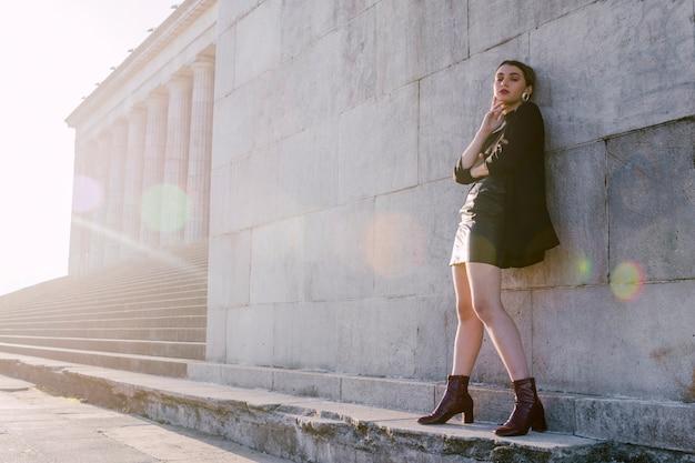 Elegante jovem de pé na parede com luz solar Foto gratuita