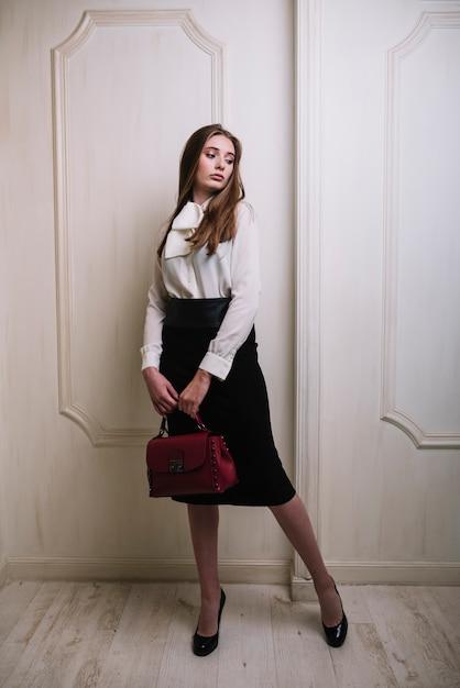 Elegante jovem de saia e blusa com bolsa na sala Foto gratuita