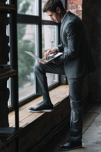Elegante jovem empresário em pé perto da janela, digitando no laptop Foto gratuita