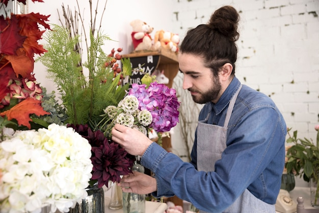 Elegante jovem florista masculina organizando as flores no buquê Foto gratuita
