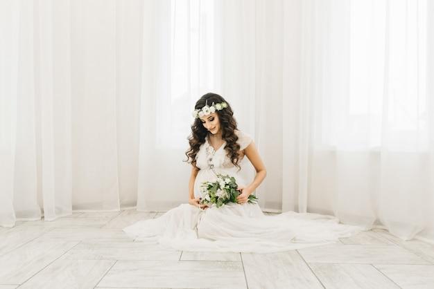 Elegante jovem grávida em roupas brancas com cachos e flores. fotos esperando bebe Foto Premium