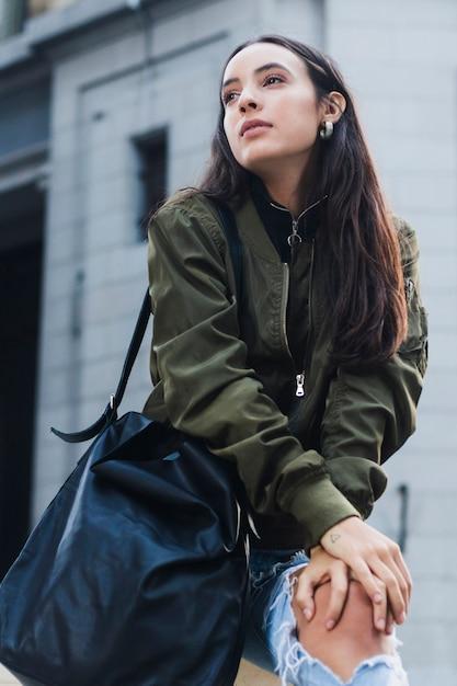 Elegante jovem mulher com a bolsa azul no ombro, olhando para longe Foto gratuita