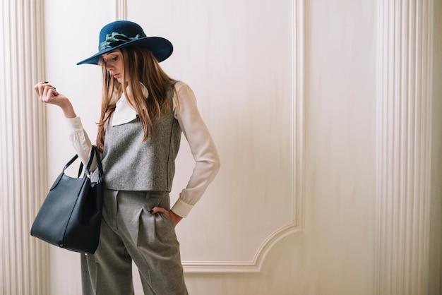 Elegante jovem mulher em traje e chapéu com bolsa no quarto Foto gratuita