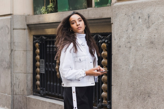 Elegante jovem segurando o celular na mão, olhando para a câmera Foto gratuita