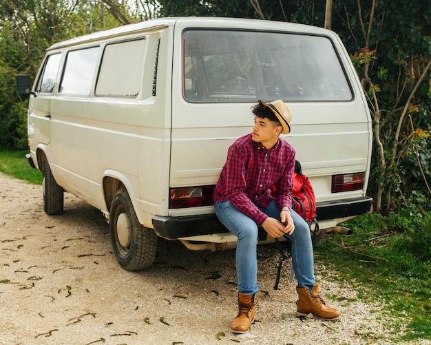 Elegante jovem sentado atrás de van Foto gratuita