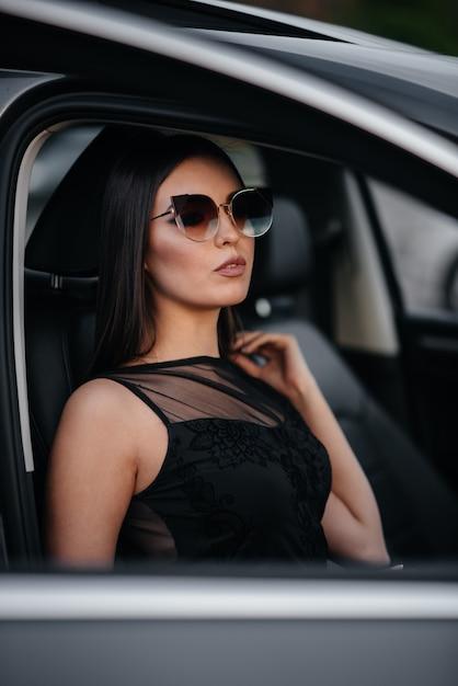 Elegante jovem sentado em um carro de classe executiva em um vestido preto. moda e estilo de negócios. Foto Premium