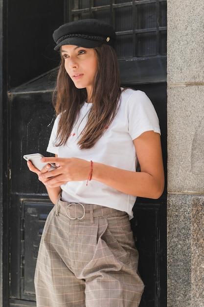 Elegante jovem vestindo boné preto, segurando o celular na mão, olhando para longe Foto gratuita
