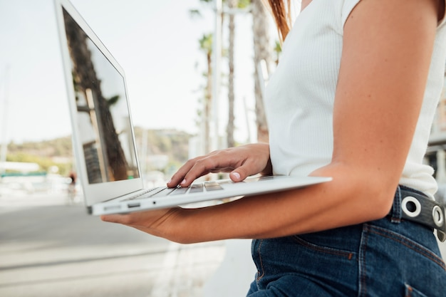 Elegante, menina jovem, segurando, um, laptop Foto gratuita