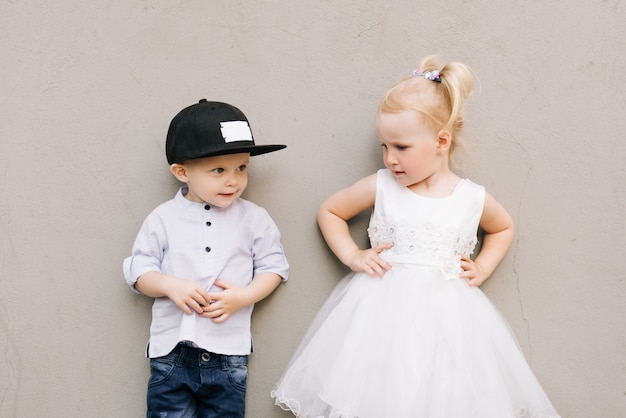 Elegante menino e menina na parede cinza Foto Premium